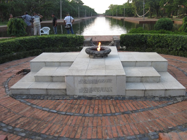 The eternal flame symbolizes world peace and sits in front of a landscaped pool that separates the Theravada and Mahayana Buddhist traditions in the International Monastic Zone.
